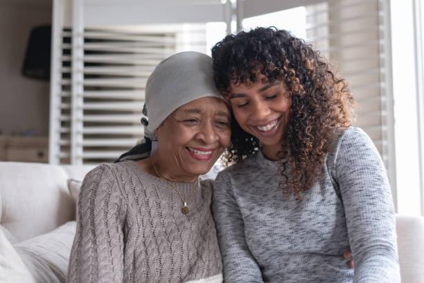 seniorenfrau mit krebs sitzend mit tochter - immunsystem stärken stock-fotos und bilder