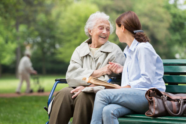Senior woman with caregiver in the park stock photo