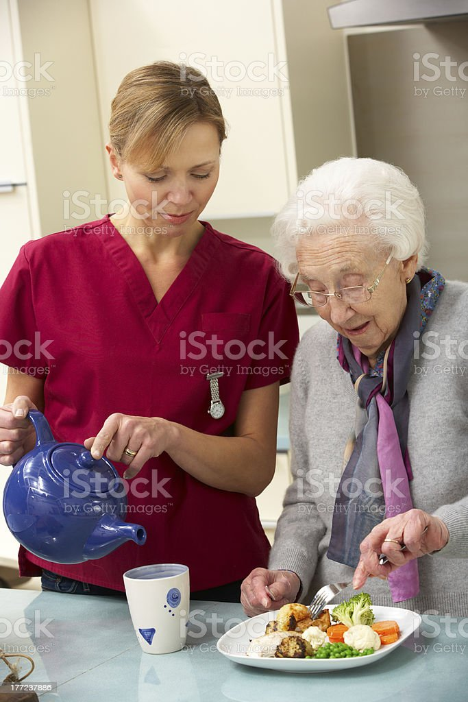 Senior woman with carer eating meal at home royalty-free stock photo