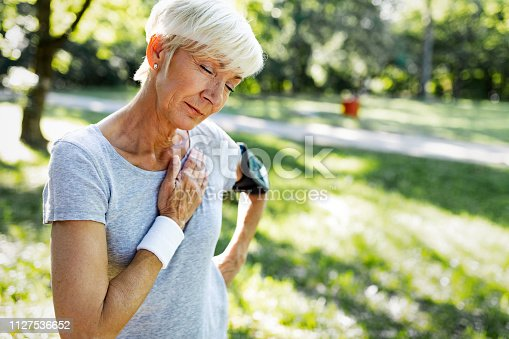 istock Senior woman with chest pain suffering from heart attack during jogging 1127536652