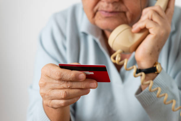 Senior Woman With Credit Card Senior woman using phone while holding credit card. elder fraud stock pictures, royalty-free photos & images