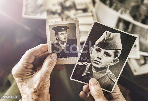 A 89 year old grandmother is holding photographs of her deceased husband at times when he was 10 and 19 (circa 1936). Toned image, AdobeRGB profile.