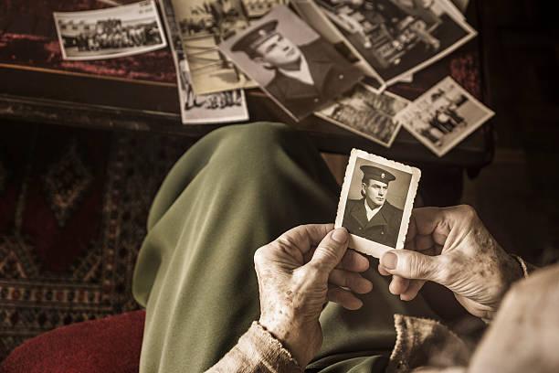 senior woman with dear photographs - senior fotoboek stockfoto's en -beelden