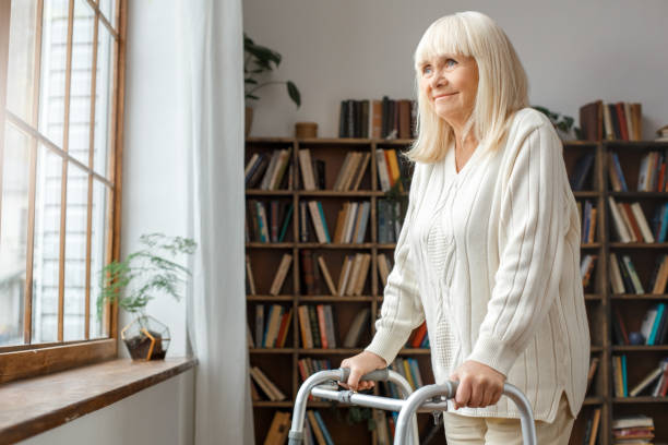 Senior woman with disability recovery at home walking frames looking out the window dreaming stock photo