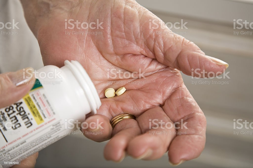 senior woman with distorted arthritis hand taking aspirin pills stock photo