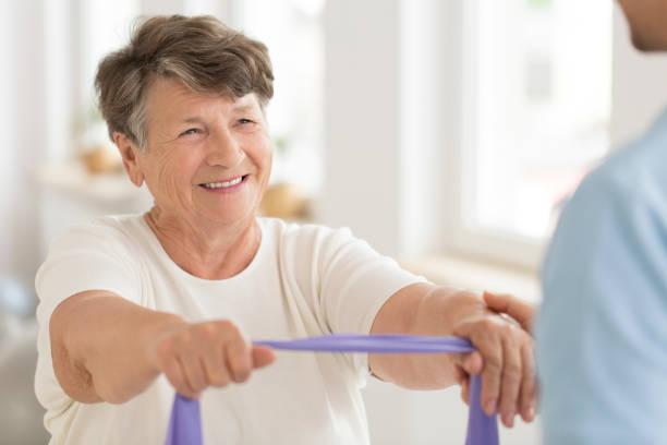 ältere frau mit gummiband - physiotherapie stock-fotos und bilder
