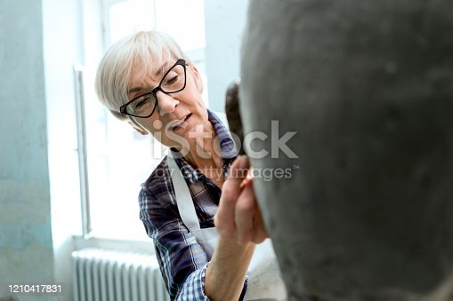 Senior woman's hands making statue of clay