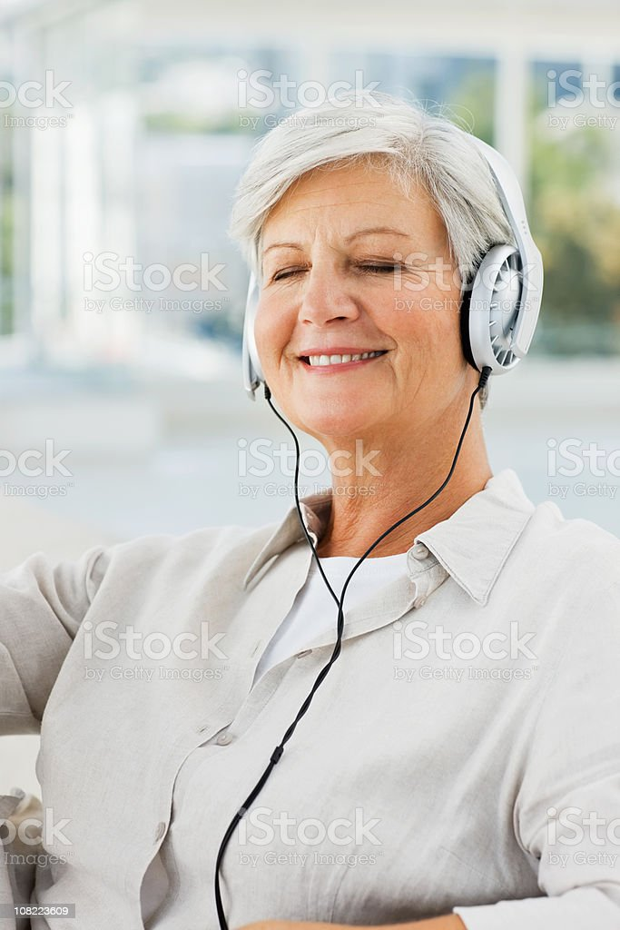 Senior woman with eyes closed listening to music royalty-free stock photo