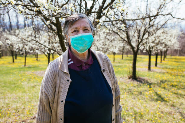 Senior woman with face mask standing in nature stock photo