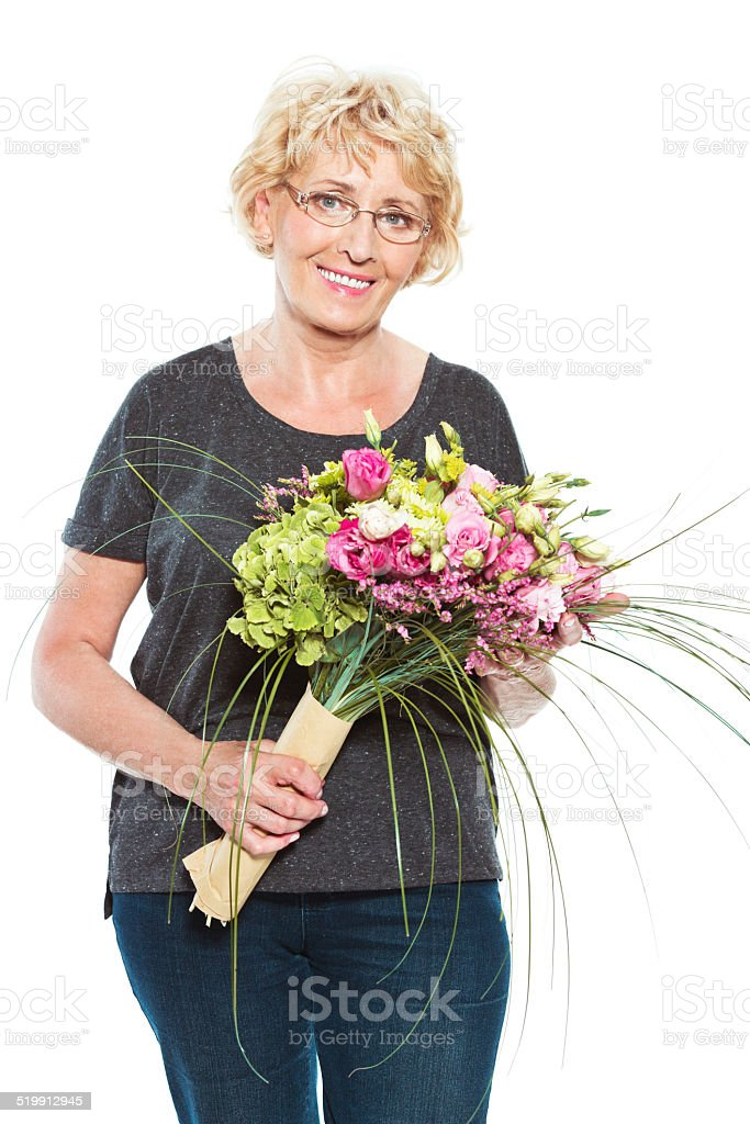 Senior woman with flowers on white background Happy senior woman holding bouquet in hands and smiling at the camera. Studio shot, white background. 60-64 Years Stock Photo