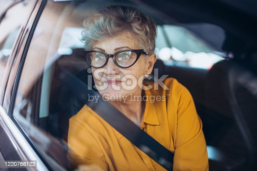 Attractive senior woman with glasses sitting in a car. Shot through glass.