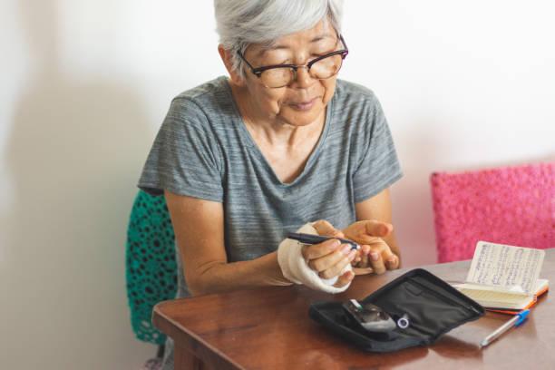 seniorenfrau mit glukometer überprüft blutzuckerspiegel zu hause - hyperglycemia stock-fotos und bilder