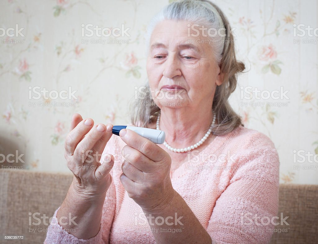 Senior woman with glucometer checking blood sugar level at home royalty-free stock photo