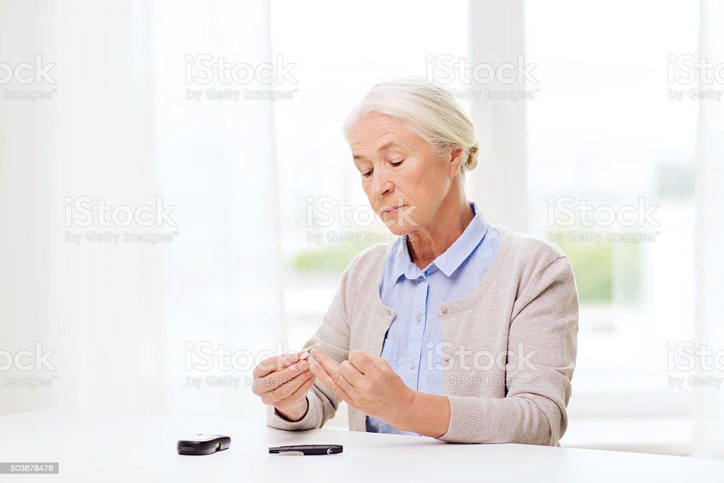 senior woman with glucometer checking blood sugar圖像檔