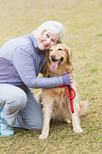 A senior woman, in her 60s with white hair, is kneeling on the grass, hugging her do, a golden retriever.  She is smiling, looking at the camera, as she holds the dog's red leash in her hand.