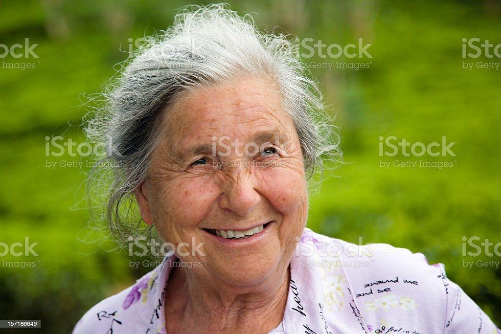 Senior Frau mit Graues Haar freundlichen Lächeln im Freien auf Grün – Foto