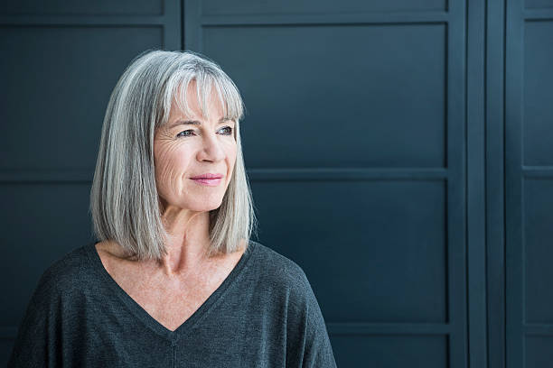Senior woman with gray hair looking away One senior woman with a grey bob in front of a dark grey background. Portrait of smart senior woman in her 60s, looking away from camera. 60 64 years stock pictures, royalty-free photos & images