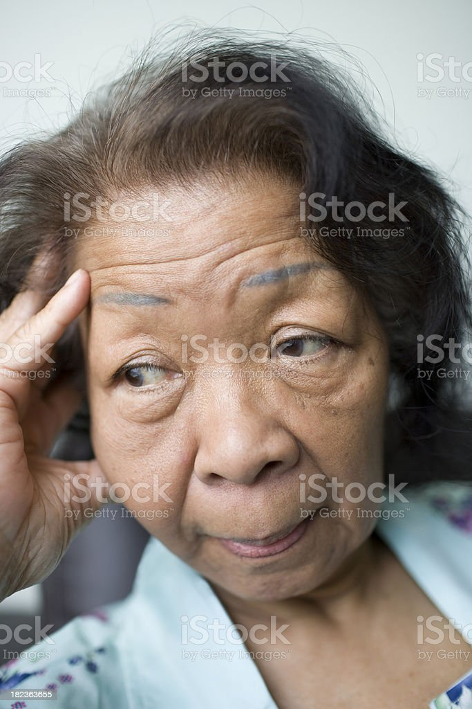 Senior woman with hand on her head and worried expression. royalty-free stock photo