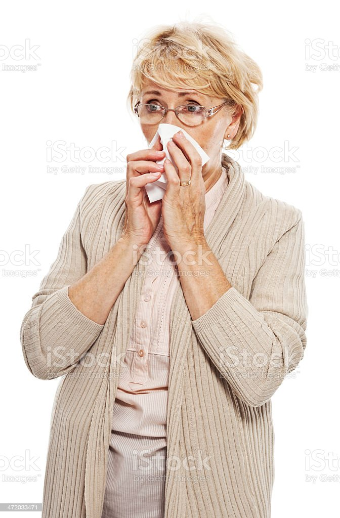 Senior woman with handkerchief Senior woman feeling unwell, blowing her nose with tissue. Studio shot, white background. 60-69 Years Stock Photo