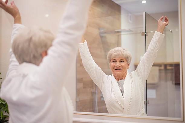 senior frau mit hände heben - alte spiegel stock-fotos und bilder
