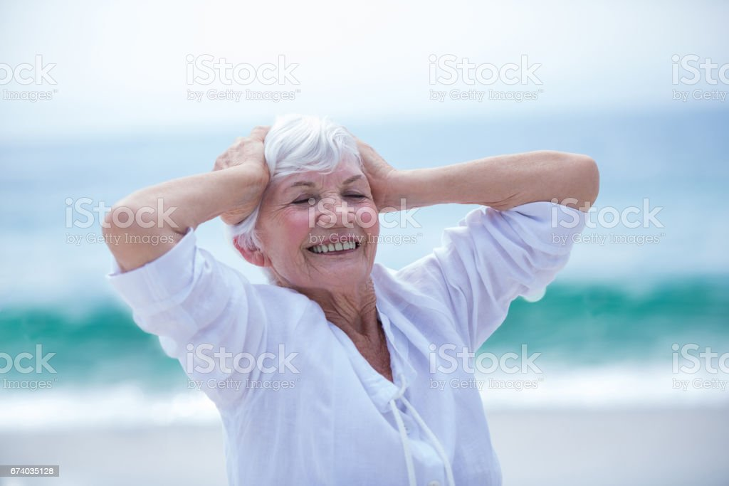 Senior woman with head in hands at sea shore royalty-free stock photo
