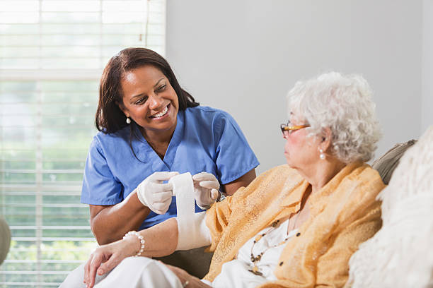 Senior woman with healthcare worker Senior Hispanic woman (70s) with Hispanic healthcare worker (50s) wrapping arm in bandage.  Focus on healthcare worker. bandage stock pictures, royalty-free photos & images