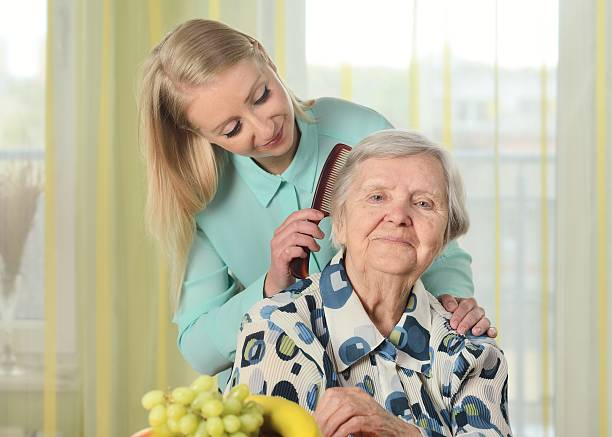 Senior woman with her caregiver in home. stock photo