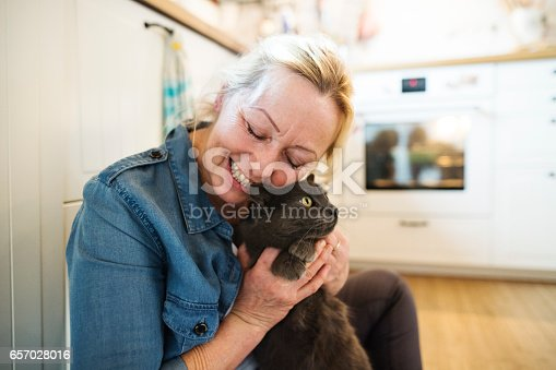 Beautiful senior woman in denim shirt with her cat at home, relaxing