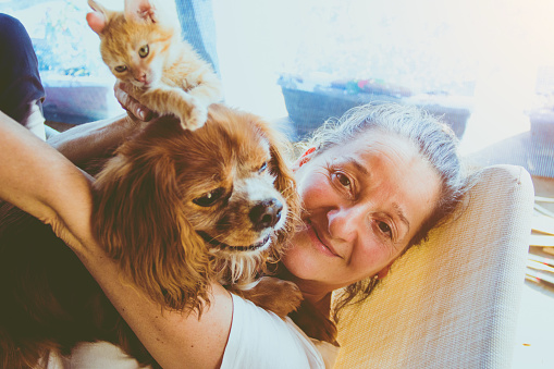 Senior woman with her cat and dog at home relaxing