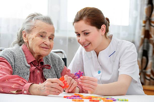 mujer senior con su personal de enfermería de atención de ancianos - geriatría fotografías e imágenes de stock