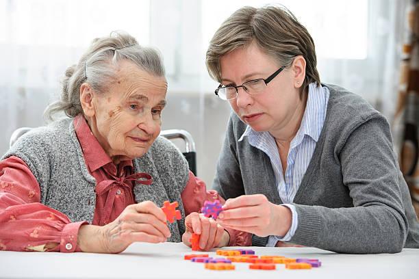 senior woman with her elder care nurse - dementia stockfoto's en -beelden