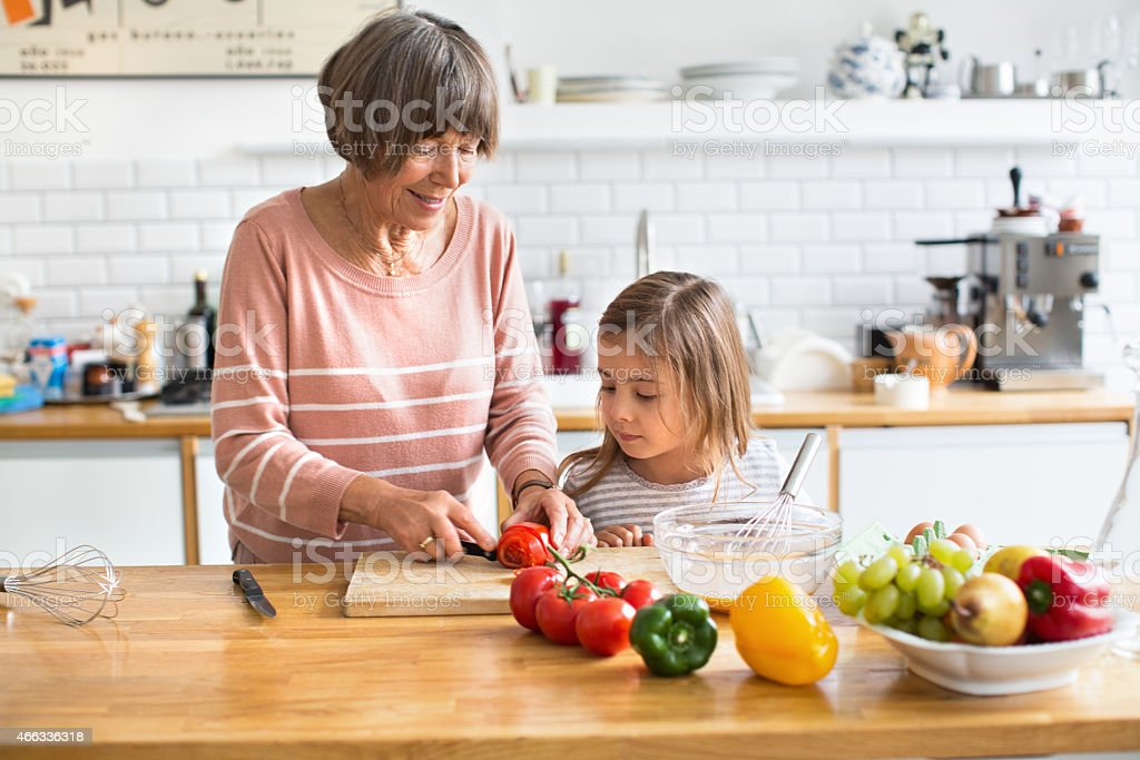 Senior woman with her granddaughter chopping vegetables in kitchen stock photo