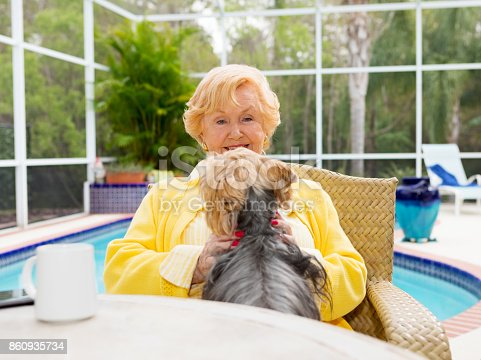 senior woman sitting with her pet dog Silky Terrier