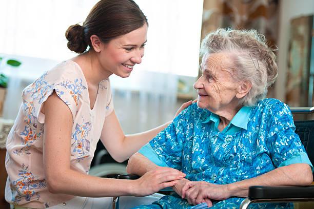 senior woman with home caregiver - thuiszorg stockfoto's en -beelden