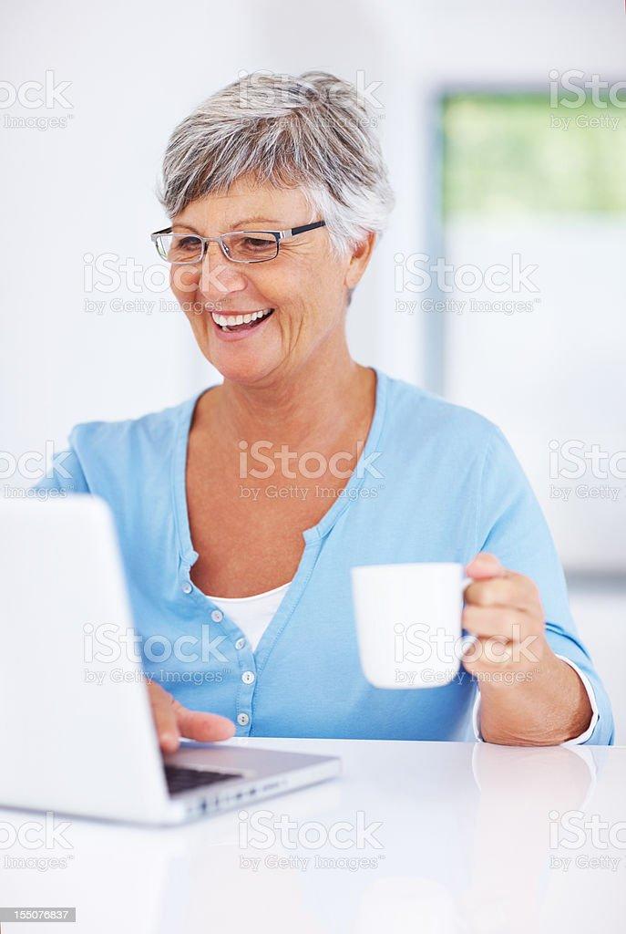 Senior woman with laptop drinking coffee royalty-free stock photo