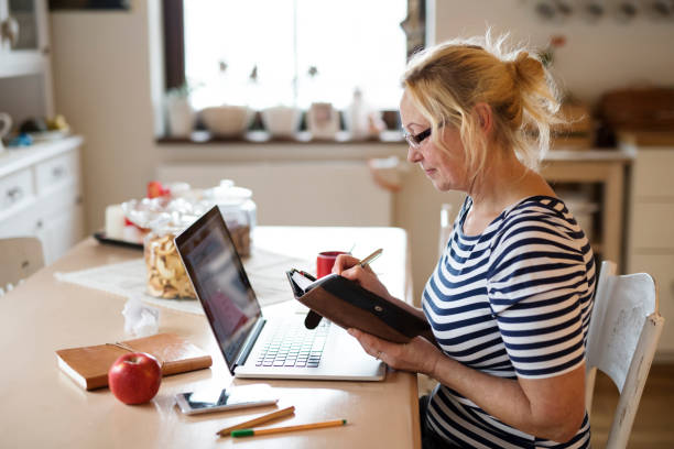 Senior woman with laptop, working at the kitchen table stock photo