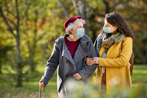 Lovely granddaughter walking with senior woman holding stick in park and wearing mask for safety against covid-19. Happy old grandmother enjoying walking in park with girl. Smiling elderly woman with happy caregiver in park relaxing after quarantine due to coronavirus outbreak and lockdown.