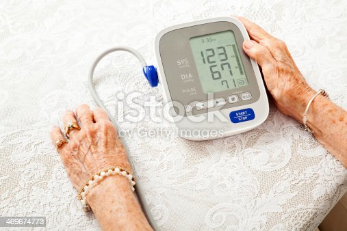 Closeup of a senior woman's hands checking her blood pressure on a home meter.  Results are low.