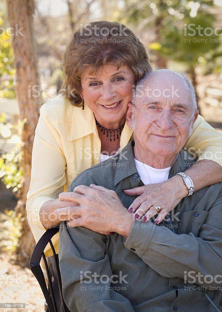 Senior Woman with Man Wearing Oxygen Tubes stock photo