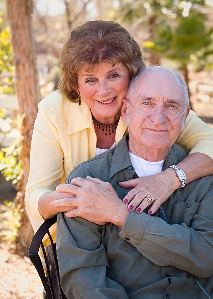 Senior Woman with Man Wearing Oxygen Tubes Senior Woman Outside with Seated Man Wearing Oxygen Tubes. medical oxygen equipment stock pictures, royalty-free photos & images