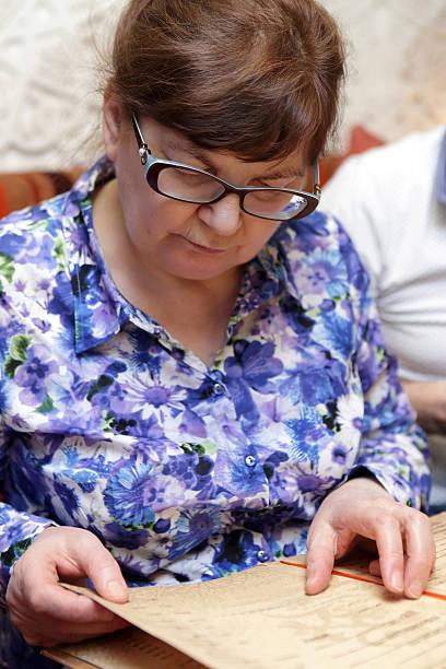 senior woman with menu - brille bestellen stock-fotos und bilder