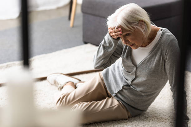 senior woman with migraine sitting on carpet and touching forehead with hand senior woman with migraine sitting on carpet and touching forehead with hand falling stock pictures, royalty-free photos & images