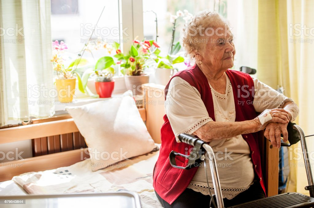 Senior Woman With Mobility Walker Sitting On Her Bed In The Retirement Community stock photo