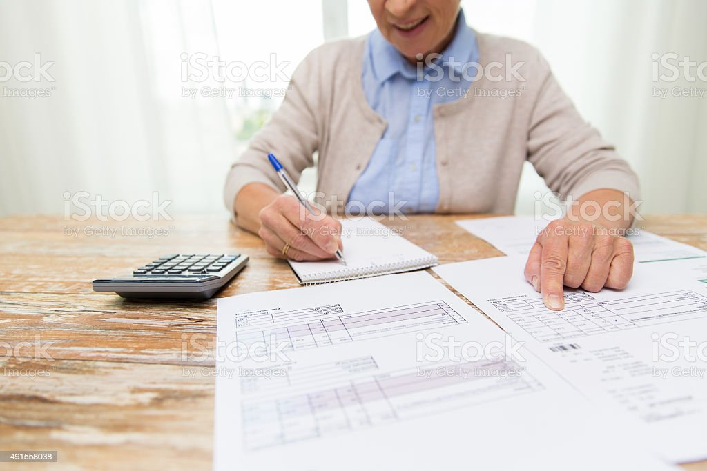 senior woman with papers and calculator at home stock photo