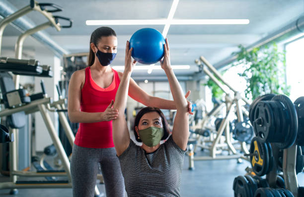Senior woman with personal trainer doing exercise in gym, coronavirus concept. stock photo