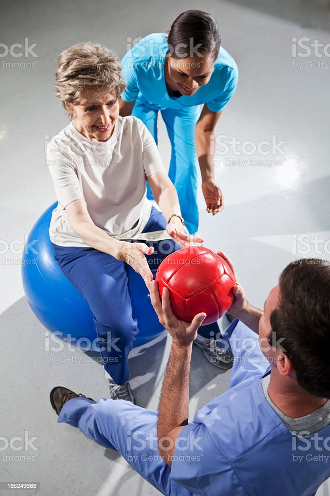 Senior woman with physical therapists using fitness balls royalty-free stock photo