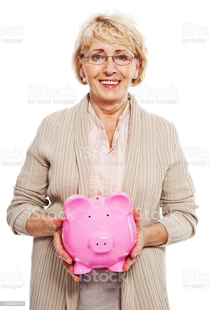 Senior woman with piggybank Portrait of happy senior woman holding a piggybank and smiling at camera. Studio shot, white background. 60-69 Years Stock Photo