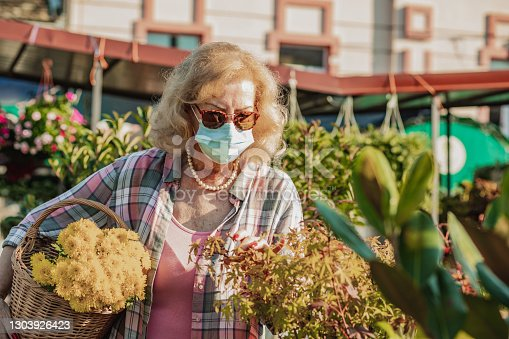 istock Senior woman with protective face mask buying flowers in spring 1303926423