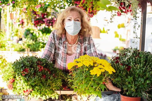 istock Senior woman with protective face mask sells flowers on the market stall 1303925414
