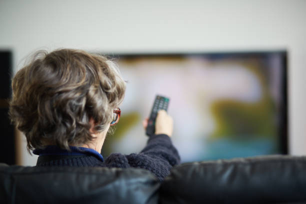 Senior woman with remote control changing channels on her TV stock photo